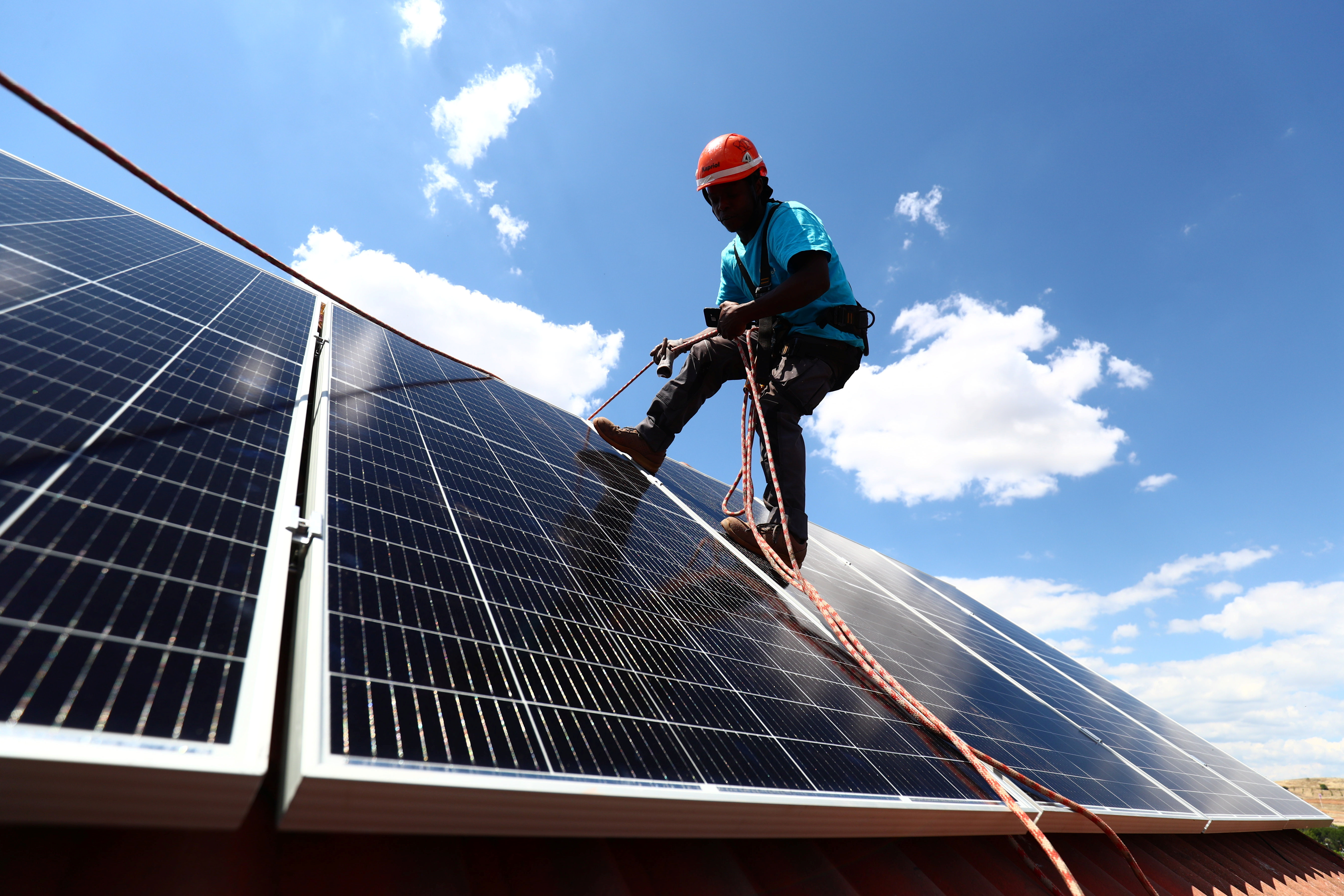 Rodrigue Kauahou, a worker of the installation company Alromar, sets up solar panels on the roof of a home in Colmenar Viejo, Spain June 19, 2020. Picture taken June 19, 2020. REUTERS/Sergio Perez - RC2HPH9UOQOH