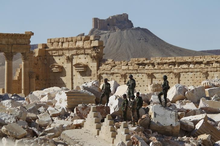 Syrian army soldiers stands on the ruins of the Temple of Bel in the historic city of Palmyra, in Homs Governorate, Syria in this April 1, 2016 file photo. The Fakhreddin's Castle is seen in the background. To match MIDEAST-CRISIS/SYRIA- INSIGHT REUTERS/Omar Sanadiki/Files