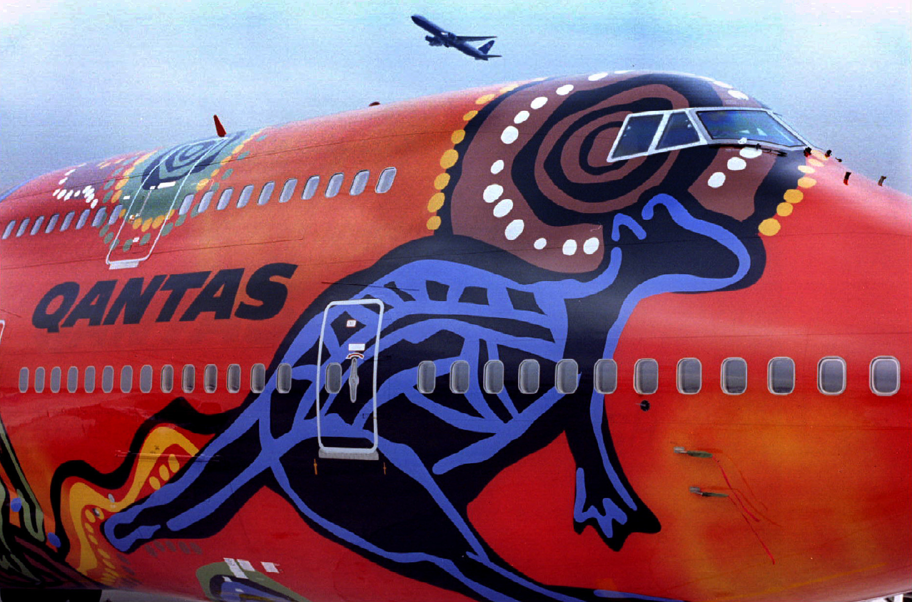 An airplane flies over a uniquely painted Quantas Boeing 747-438 during a presentation at Frankfurt's Rhein-Main airport on September 6. The so-called 'Wunala Dreaming' airplane was styled by Australian Aborigines - PBEAHUNHQAL