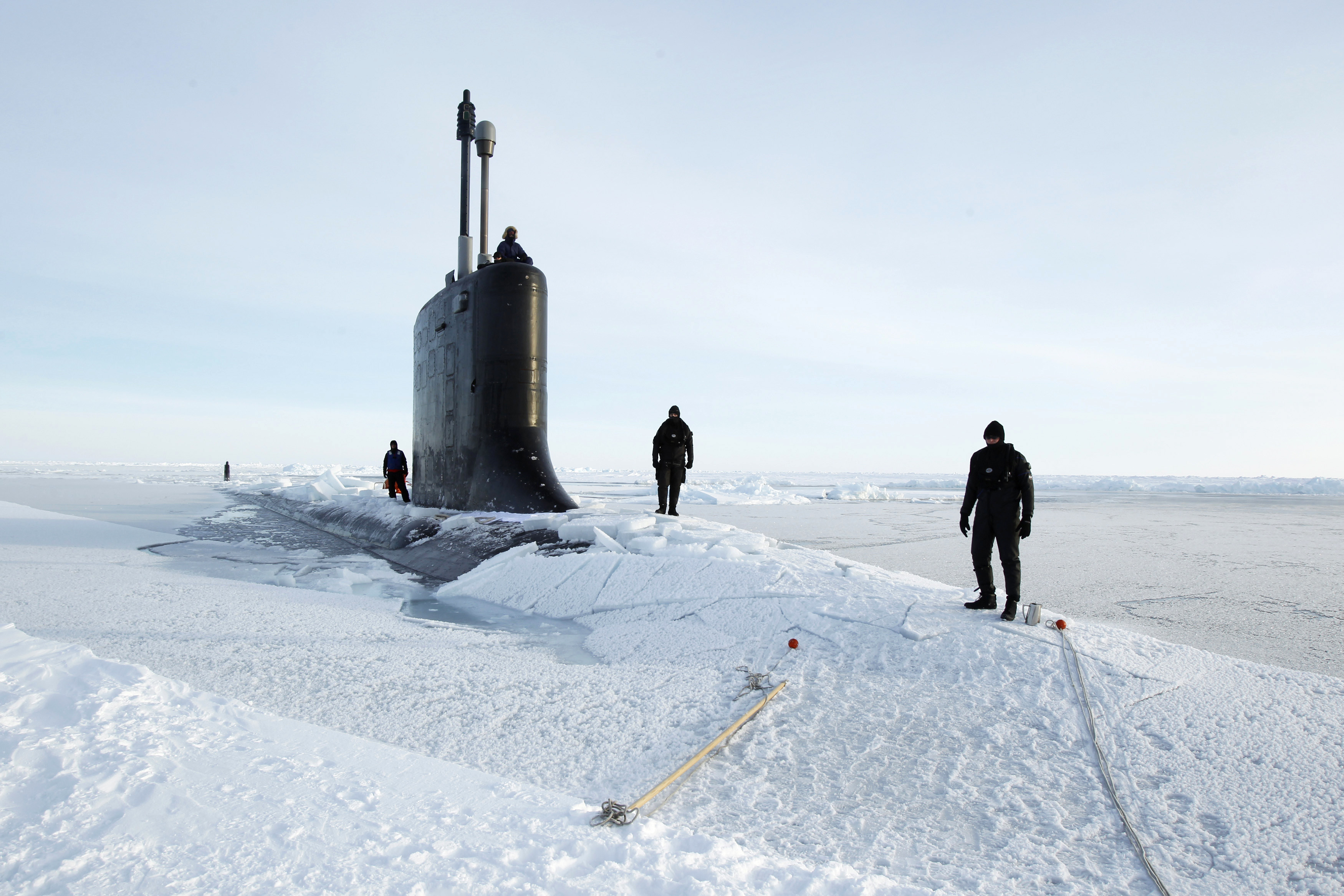 U.S. Navy safety swimmers stand on the deck of the Virginia class submarine USS New Hampshire after it surfaced through thin ice during exercises underneath ice in the Arctic Ocean north of Prudhoe Bay, Alaska March 19, 2011.  REUTERS/Lucas Jackson (UNITED STATES - Tags: MILITARY)   FOR BEST QUALITY AVAILABLE: ALSO SEE GM1E73U0AH201 - GM1E73M0IBL01
