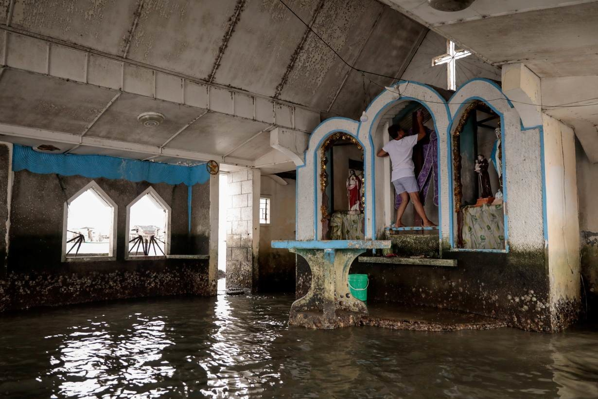 Nancy Manalaysay, 54, a church caretaker, cleans a crucifix in a partly submerged church in the coastal village Sitio Pariahan, Bulakan Bulacan, north of Manila, Philippines, November 26, 2019.