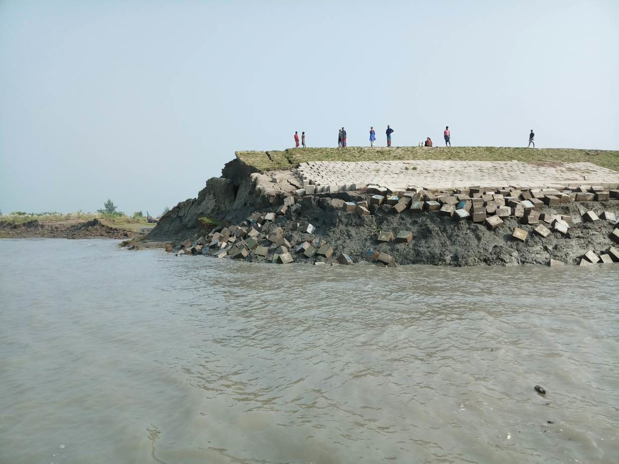 Islanders stand on an embankment on Hatiya Island that is crumbling into the sea due to erosion in Noakhali District, Bangladesh, Oct. 22, 2018,