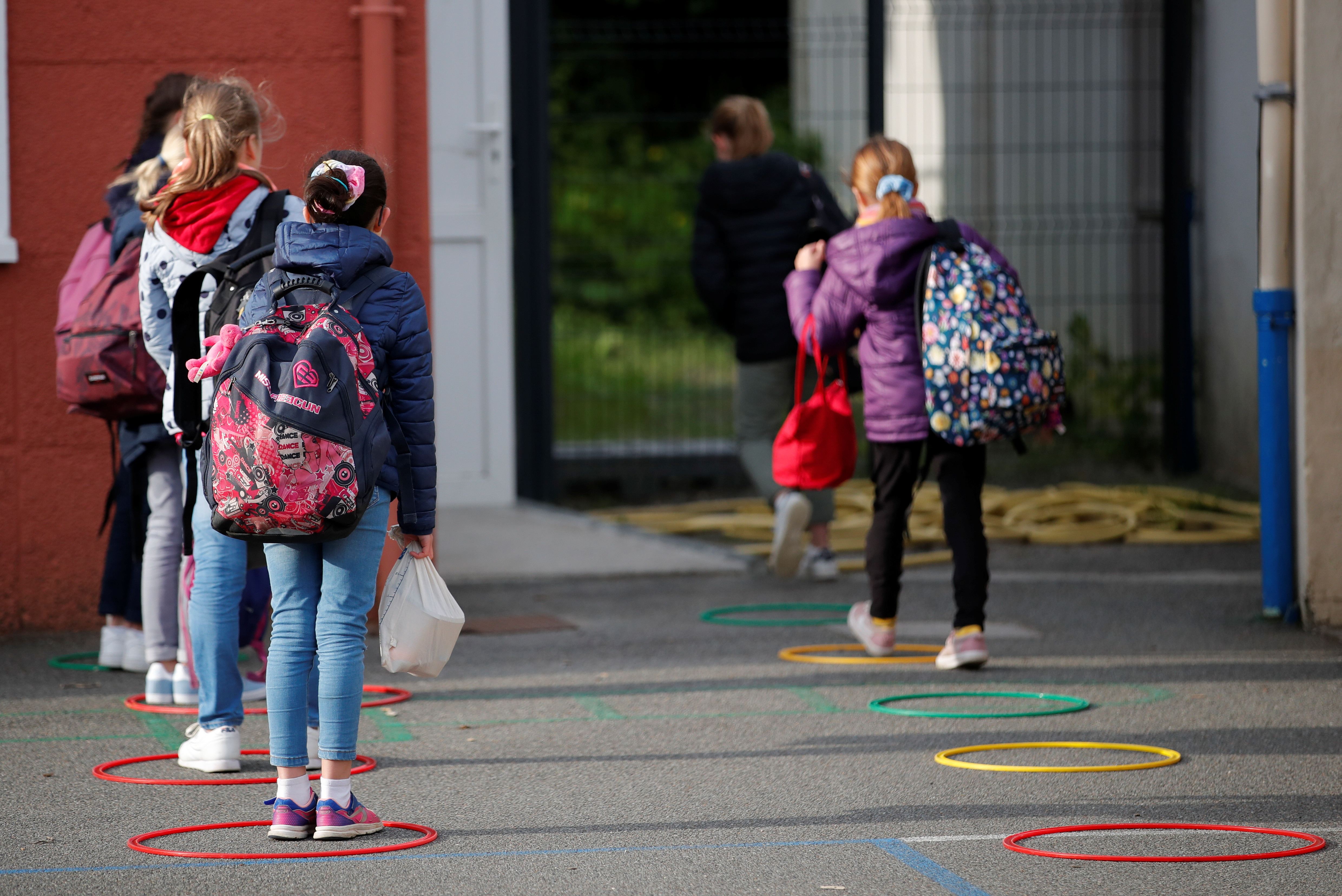 Schoolchildren line up to enter their school during its reopening in Saint-Sebastien-sur-Loire near Nantes as a small part of French children head back to their schools with new rules and social distancing during the outbreak of the coronavirus disease (COVID-19) in France, May 12, 2020. REUTERS/Stephane Mahe - RC2XMG9FH9WO