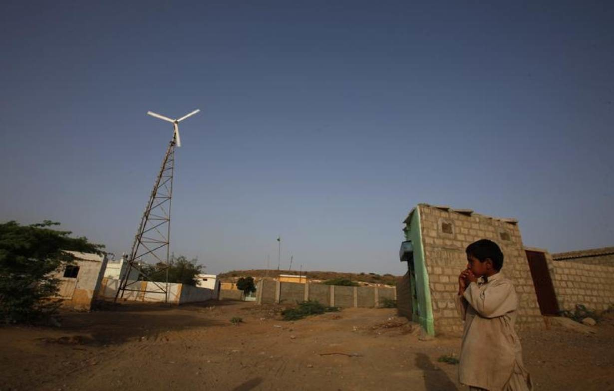 A boy stands near a wind turbine that produces energy in a village at Hub about 25 km (15 miles) northwest of Karachi June 18, 2010.