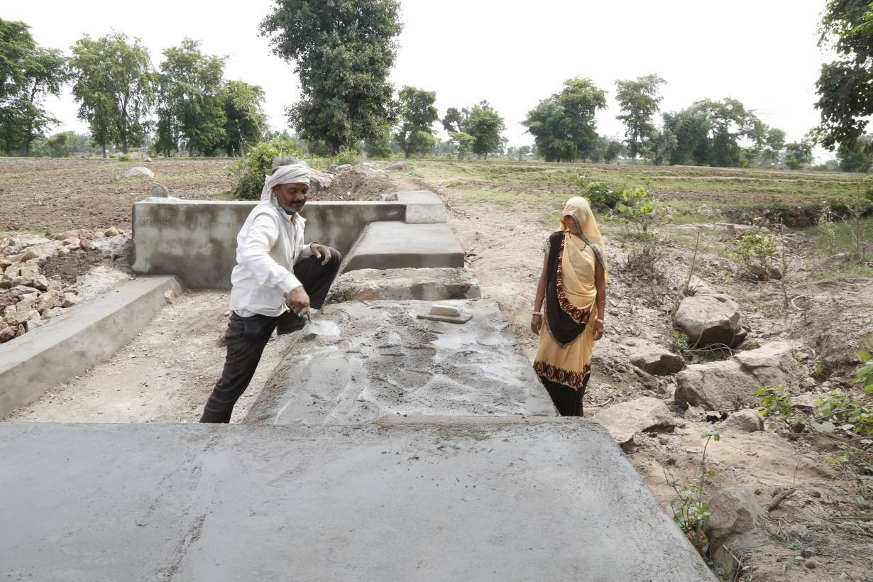 Kiran Aherwal, a Jal Saheli, or a woman water friend, supervises the making of a water outlet in Agroutha village of Bundelkhand, India on July 16, 2019.