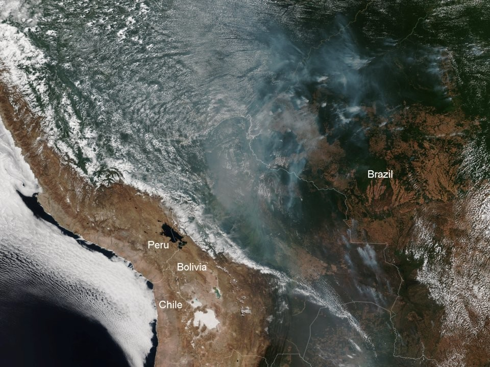 A satellite image from the NOAA shows parts of the western Amazon rainforest on fire on August 12.