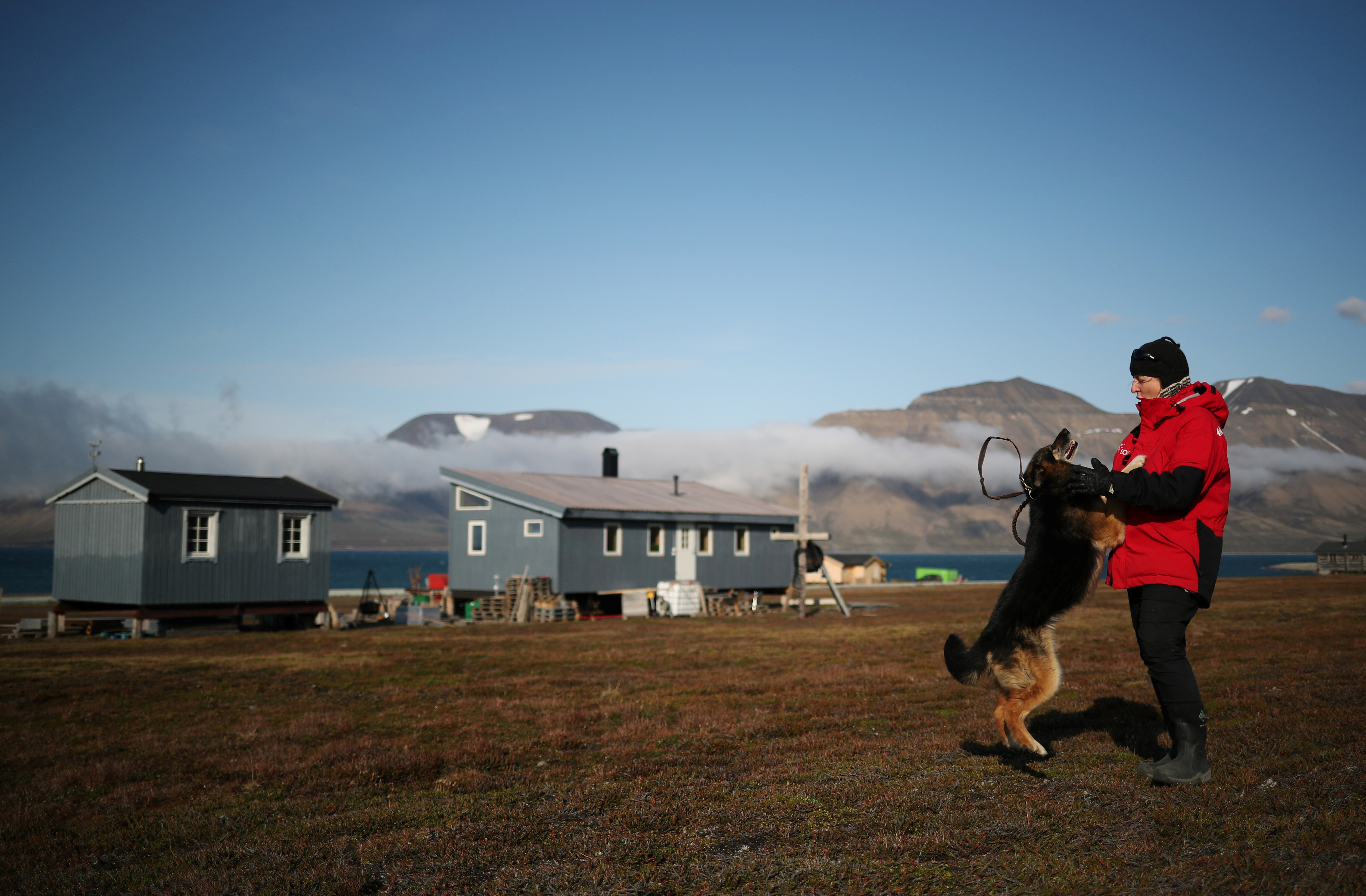 Christiane Huebner plays with her dog Svea in front of her home in the town of Longyearbyen, in Svalbard, Norway, August 3, 2019. Three years ago, as winter approached, 13 meters of coastline fell away overnight, leaving Huebner's cabin perilously close to the fjord. Huebner, her family of three and their husky dogs abandoned the home.