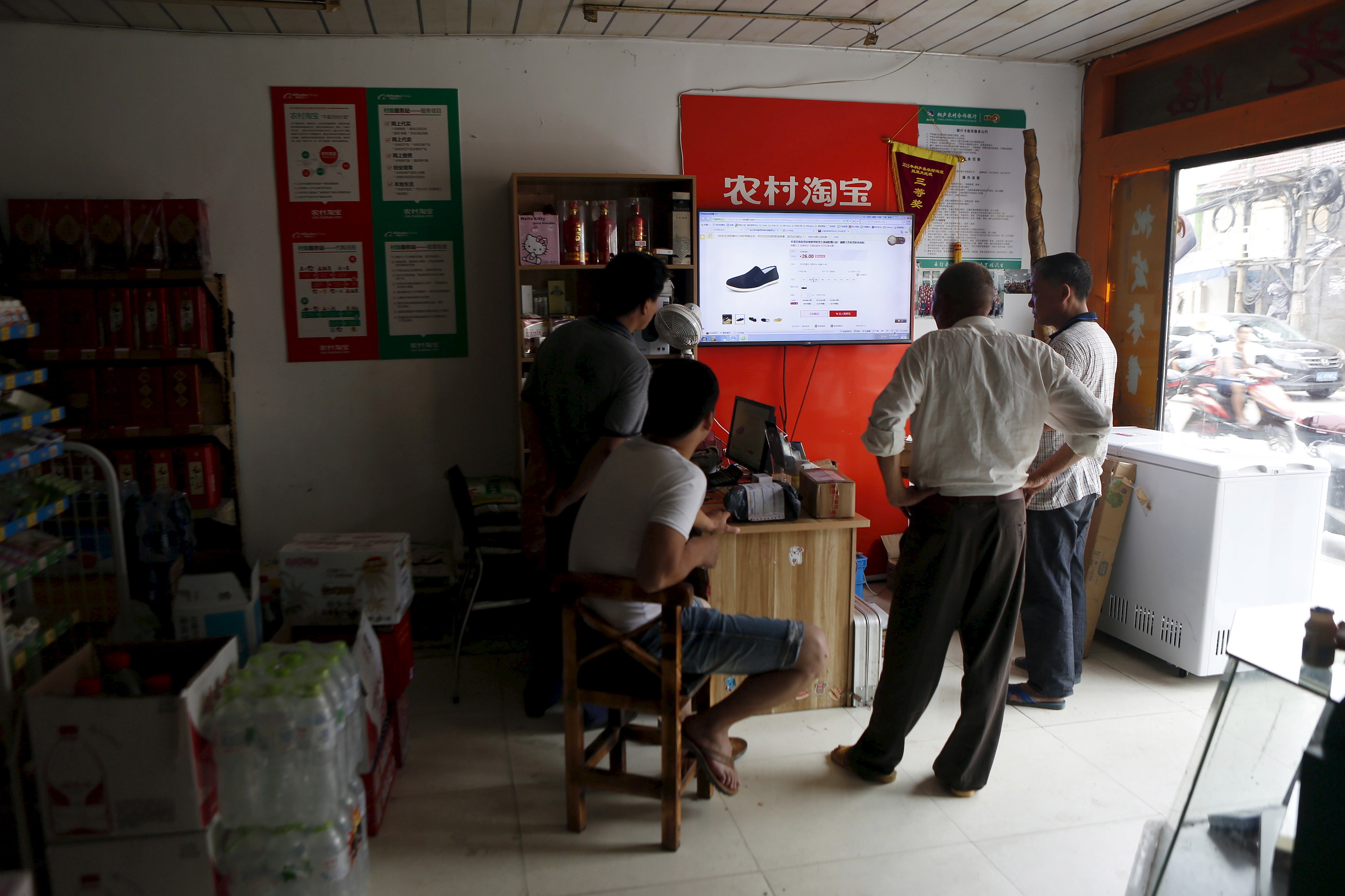 Villagers look at a screen displaying a website of Alibaba's Taobao at a rural service centre in Yuzhao Village, Tonglu, Zhejiang province, China, July 20, 2015. E-commerce growth in the countryside now outpaces that in major cities, though fewer than one tenth of online purchases made on Alibaba platforms were shipped to rural areas in the first quarter of this year. Alibaba estimates the potential market at 460 billion yuan ($74 billion) by next year. Picture taken July 20. REUTERS/Aly Song - RTX1MHA8