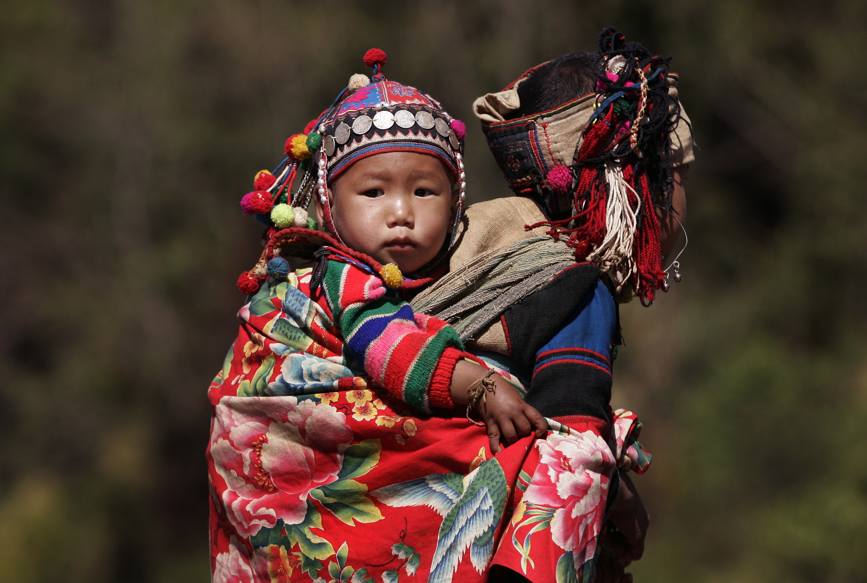 An Akha hills tribe girl carries her sibling in the Phongsali province of Laos February 15, 2006. [Laos, the world's third largest heroin producer only ten years ago, declared itself free of opium poppies on Tuesday, after a six year campaign against the raw material use to make the narcotic.] - RTXO985