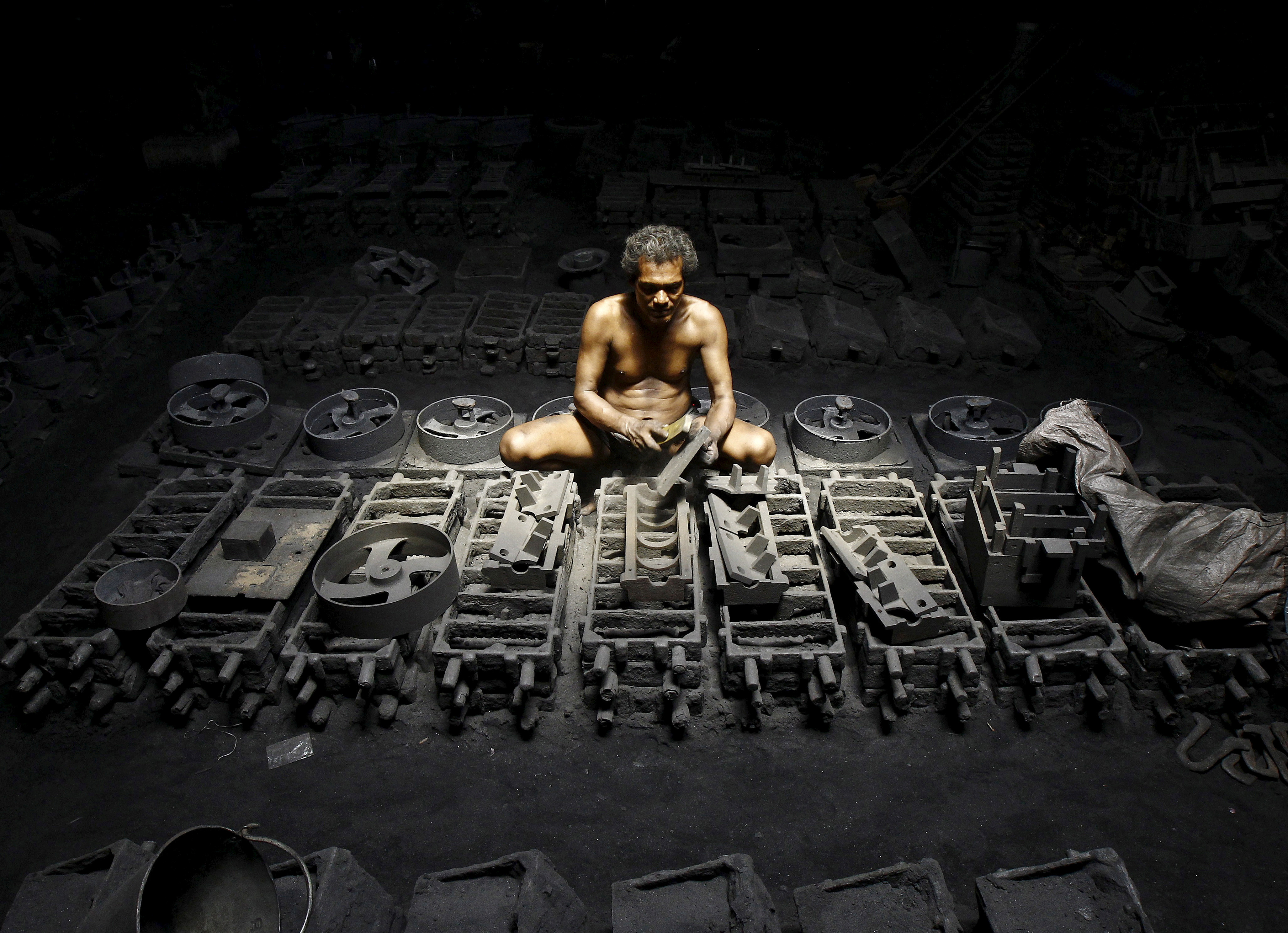 A labourer works inside the manufacturing unit of iron parts at a factory on the outskirts of Kolkata, India, September 11, 2015. REUTERS/Rupak De Chowdhuri/File Photo   GLOBAL BUSINESS WEEK AHEAD PACKAGE - SEARCH