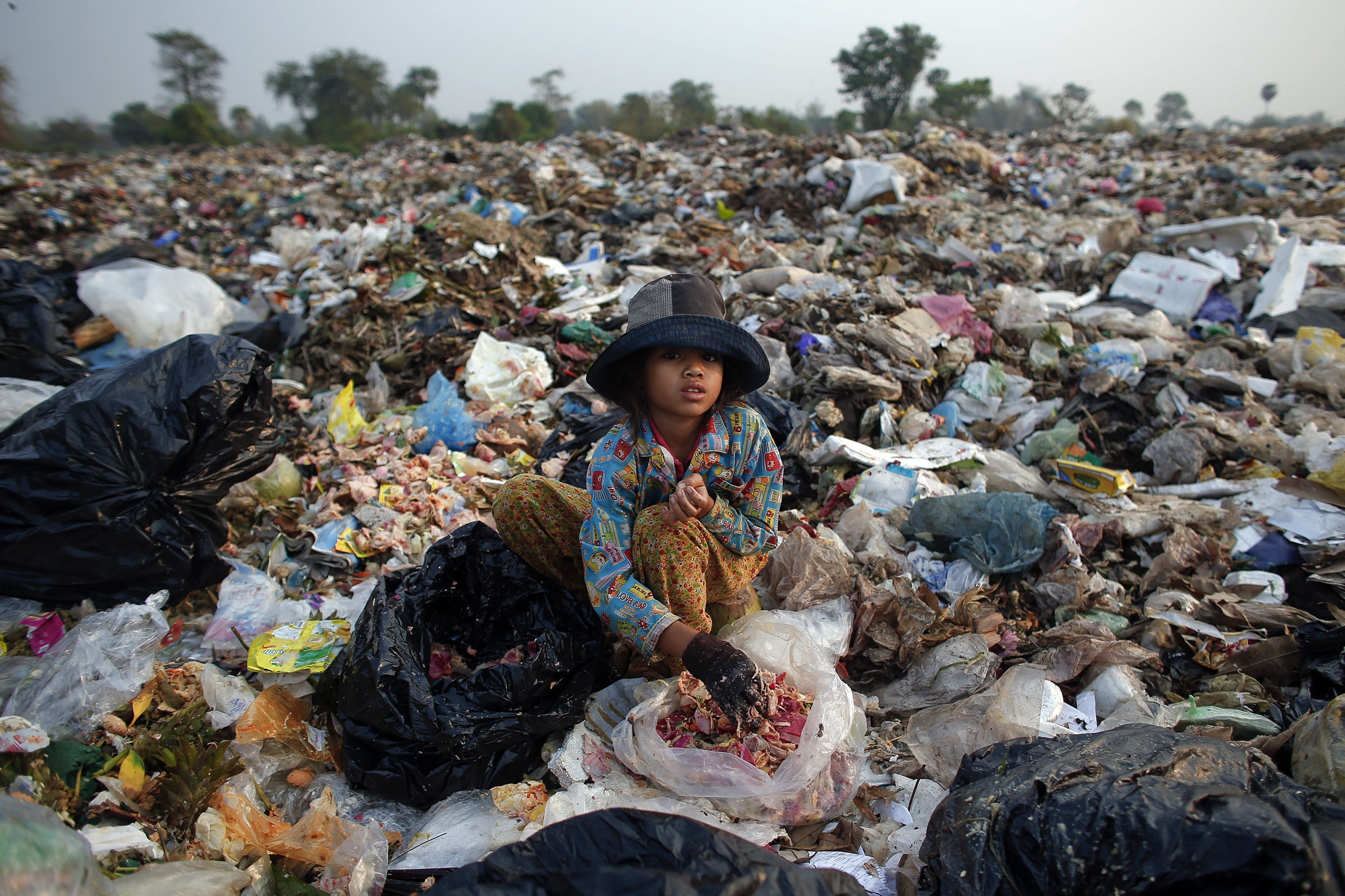 Soburn, an 11-year-old girl, collects what can be used as food for pigs at landfill dumpsite outside Siem Reap March 19, 2015. A second-grade student, she helps her parents in the morning collecting usable items at the dumpsite where they live before going to school in the afternoon. Anlong Pi, an eight-hectare dumpsite situated close to the famous Cambodian resort province of Siem Reap, has recently become a tourist attraction in its own right. Sightseers pose for pictures with children who scavenge scraps for a living, making between $0.25 and $2 per day, according to a representative of a company overseeing the waste. Michelle Obama is due to visit to Cambodia to promote Let Girls Learn, a worldwide initiative that aims to help adolescent girls attend school.   REUTERS/Athit PerawongmethaPICTURE 8 OF 23 FOR WIDER IMAGE STORY 'LIVING ON RUBBISH'SEARCH 'ANLONG PI' FOR ALL IMAGES - RTR4U4KB