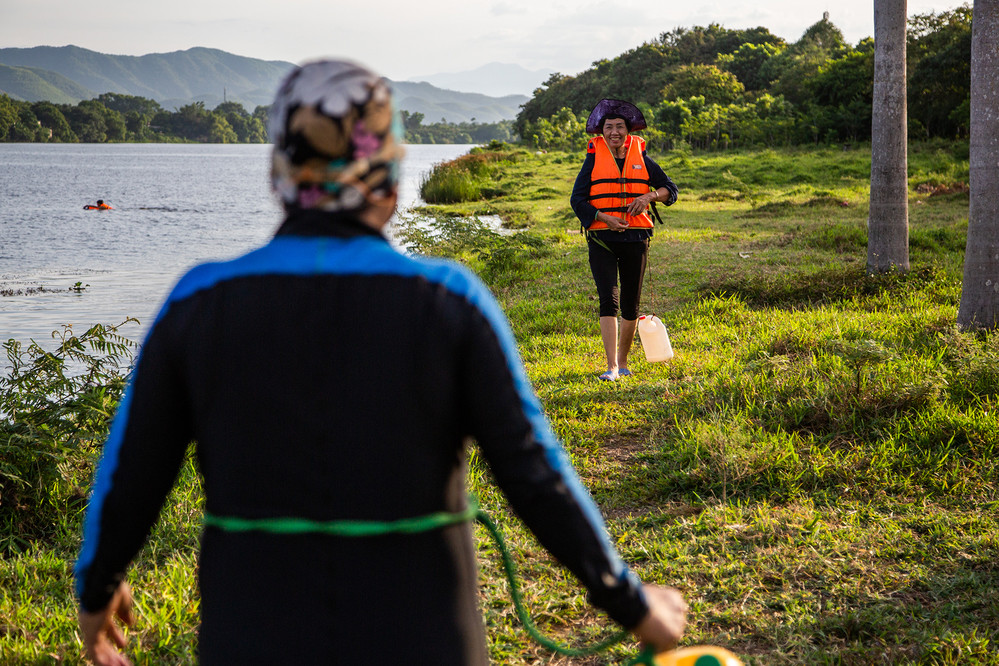Women meet up in the evening on the banks of the Perfume River in Hue. A group of them swim every morning and evening in the river and work to collect rubbish and keep the riverside clean.