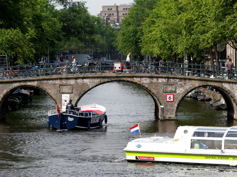 FILE PHOTO: Tourists boats pass on a canal in Amsterdam, Netherlands, May 16, 2018. Picture taken May 16, 2018.  REUTERS/Francois Lenoir/File Photo