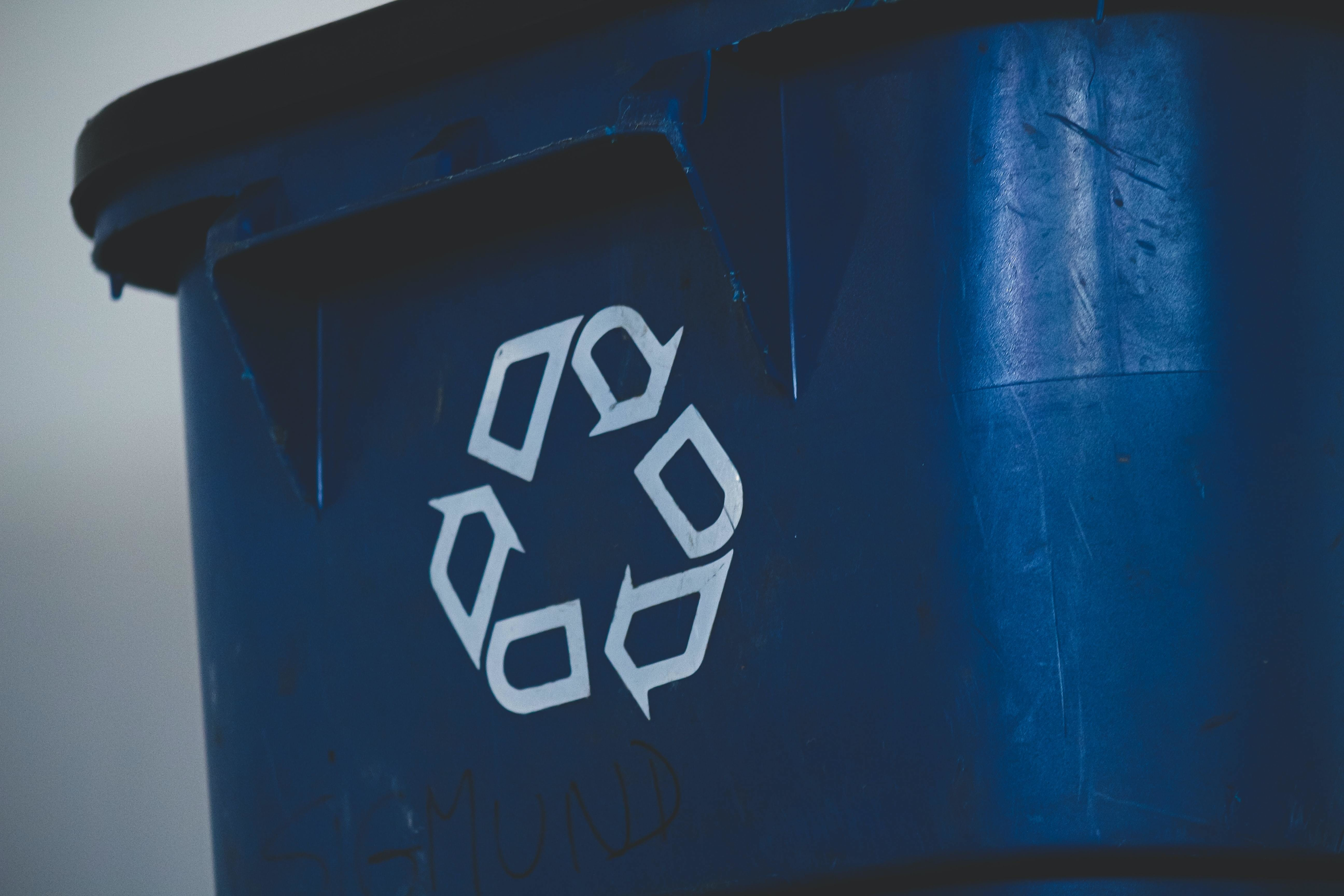 White three-arrow recycling symbol on a dark blue bin.