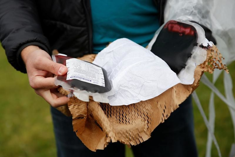 Keenan Wyrobek, head of product engineering at Zipline International, displays a package of fake blood airdropped by a Zipline drone during a flight demonstration at an undisclosed location in the San Francisco Bay Area, California, U.S., May 5, 2016. REUTERS/Stephen Lam - S1AETDANIRAB