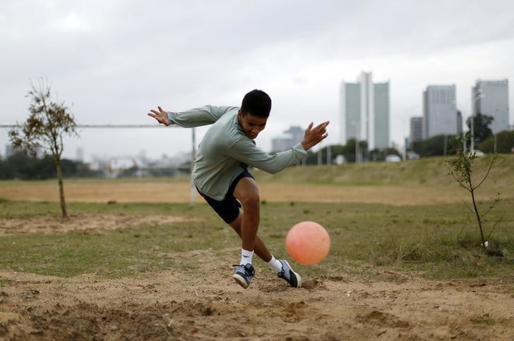 A boy plays soccer in a park in Porto Alegre June 16, 2014. In a project