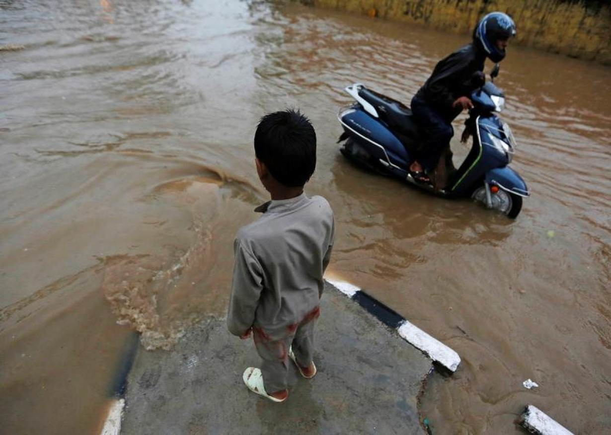 A boy stands on a divider as a man pushes his scooter through a flooded street during heavy rains in New Delhi, India, August 29, 2016.
