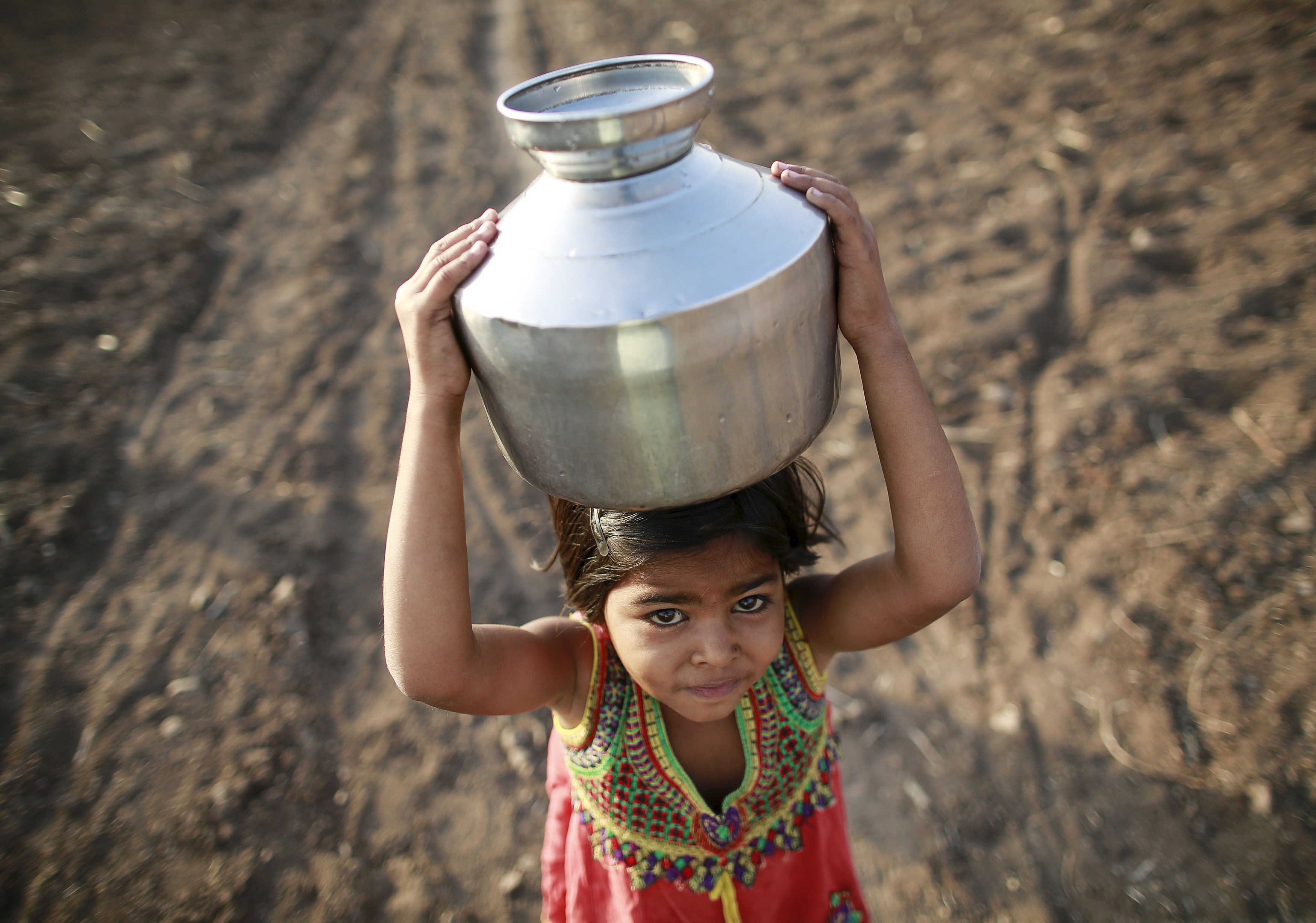 A girl carries a metal pitcher filled with water through a field in Latur