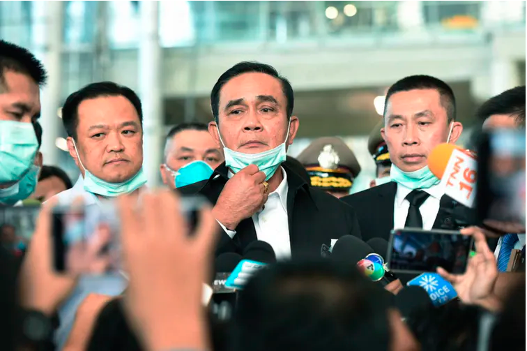 Thailand Prime Minister Prayuth Chan-ocha, centre, removes his face mask to speak to journalists during a visit to the Suvarnabhumi International airport to inspect measures in place to monitor passengers for the coronavirus.