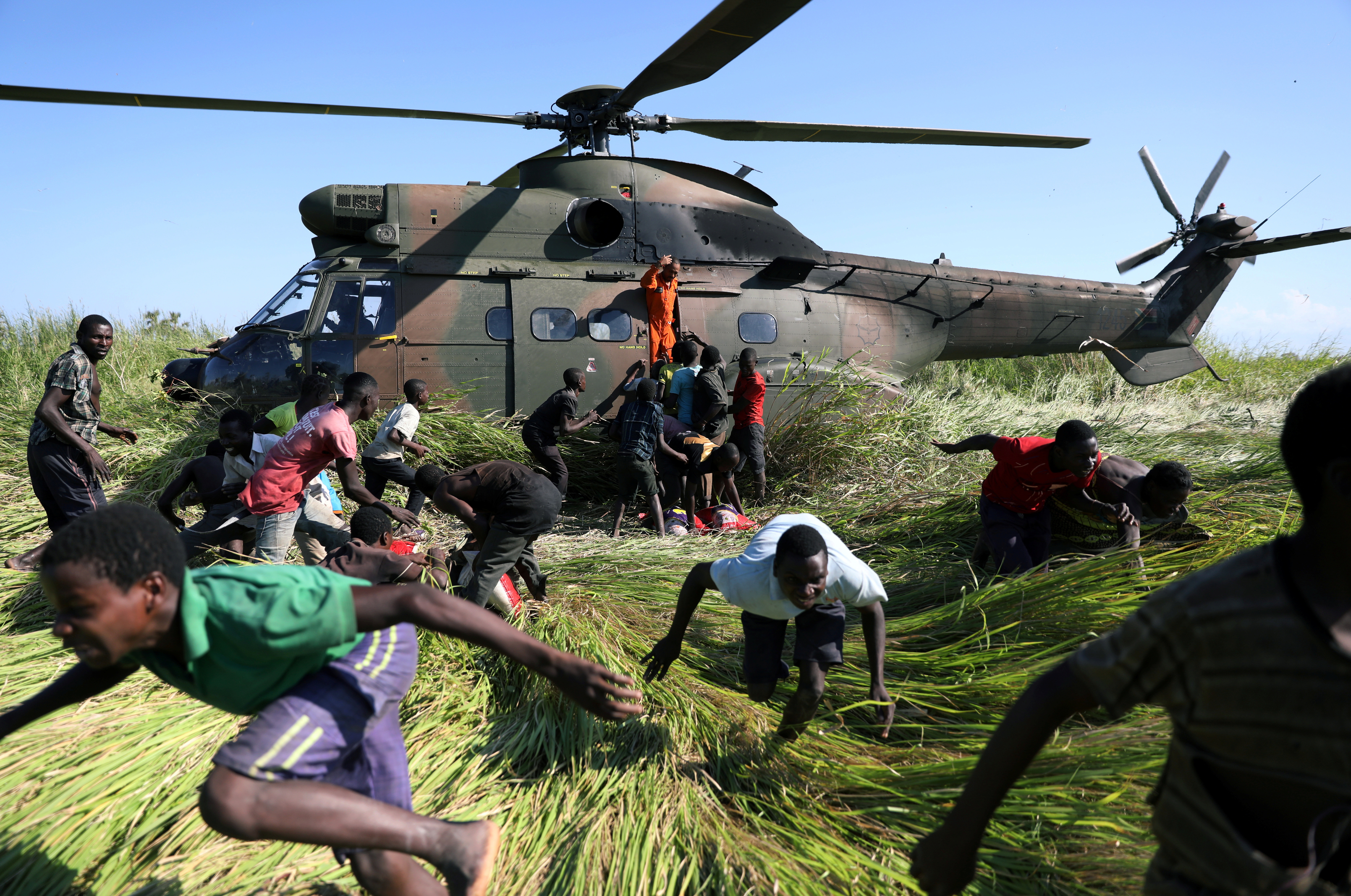 People run after collecting food aid from a South African army helicopter in the aftermath of Cyclone Idai in Mozambique, March 2019.