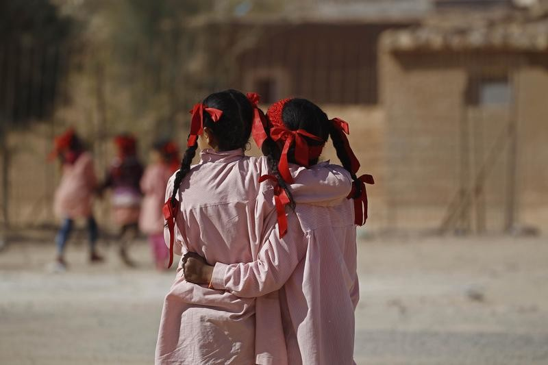 Indigenous Sahrawi girls hug each other beside their school in a refugee camp of Boudjdour in Tindouf, southern Algeria March 3, 2016. UN Secretary General Ban Ki-moon is scheduled to visit the Sahrawi refugees in south-west Algeria's Tindouf region. REUTERS/Zohra Bensemra - D1AESQKLLRAA