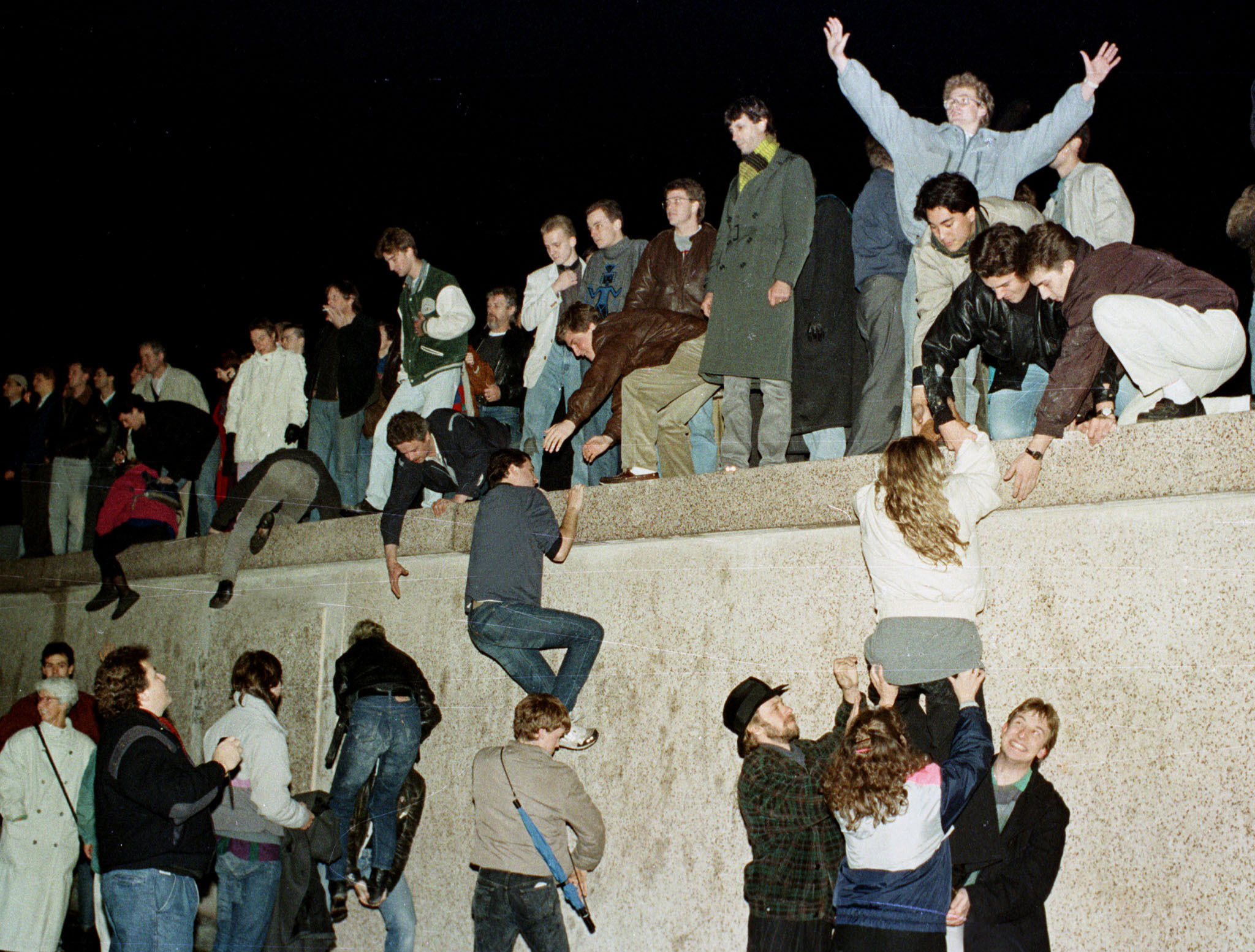 East German citizens climb the Berlin wall at the Brandenburg Gate as they celebrate the opening of the East German border in November 1989