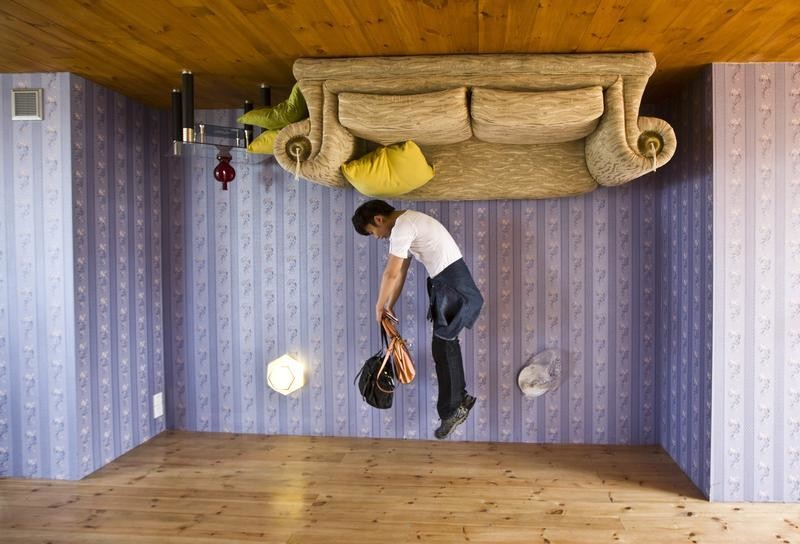 A tourist jumps inside an upside-down house at Fengjing Ancient Town, Jinshan District, south of Shanghai, May 1, 2014. The upside-down house was built as a tourist attraction using everyday household items and furniture. REUTERS/Aly Song  (CHINA - Tags: SOCIETY TPX IMAGES OF THE DAY TRAVEL) - GF2EA510PX301