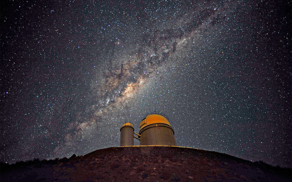 "The ESO 3.6-metre telescope at La Silla, during observations. Across  the plan of the picture, is the Milky Way, our own galaxy, a disc-shaped  structure seen perfectly edge-on. Above the telescope´s dome, here  lighted by the Moon, and partially hidden behind dark dust clouds, is  the yellowish and prominent central bulge of the Milky Way. The whole  plan of the galaxy is populated by hundred thousand million of stars, as  well as a conspicuous amount of interstellar gas and dusts. The dust  absorbs the visible light and reemits it at longer wavelength, appearing  totally opaque at our eyes. The ancient Andean civilizations saw in  these dark lanes their animal-shaped constellations. By following the  dark lane which seems to grow from the centre of the Galaxy toward the  top, we find the reddish nebula around Antares (Alpha Scorpii). The  Galactic Centre itself lies in the constellation of Sagittarius and  reaches its maximum visibility during the austral winter season. The ESO  3.6-metre telescope, inaugurated in 1976, currently operates with the  HARPS spectrograph, the most precise exoplanet ""hunter"" in the world.  Located 600 km north of Santiago, at 2400 m altitude in the outskirts of  the Chilean Atacama Desert, La Silla was first ESO site in Chile and  the largest observatory of its time. This photograph was taken by ESO Photo Ambassador Serge Brunier. Links  ESO Photo Ambassadors webpage."