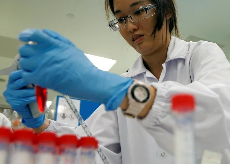 An employee conducts tests at a laboratory in a pharmaceutical manufacturing factory in Singapore April 17, 2017.