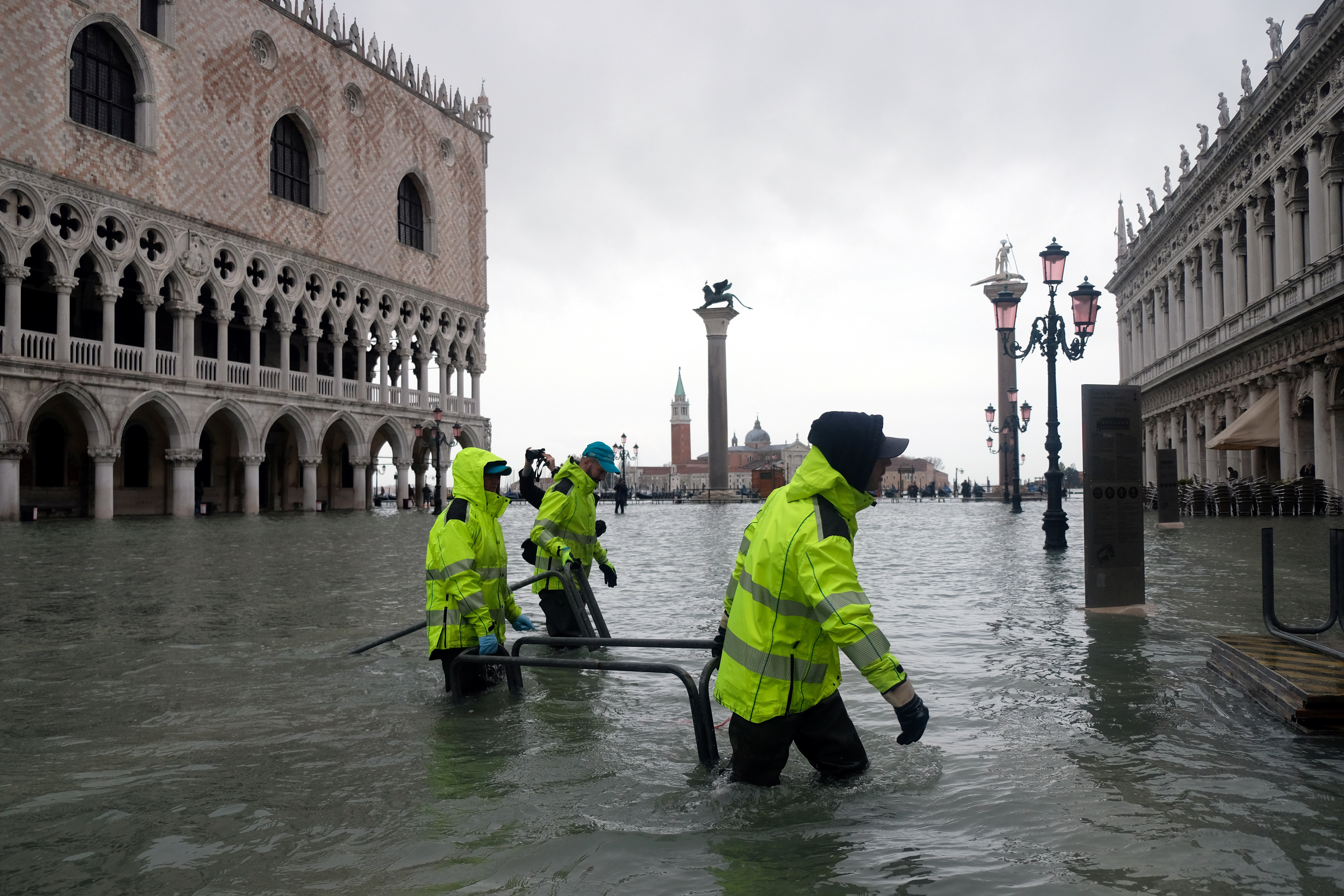Workers wade through a flooded St. Mark's Square during a period of seasonal high water in Venice, Italy November 24, 2019. REUTERS/Manuel Silvestri - RC2KHD9H0AYY