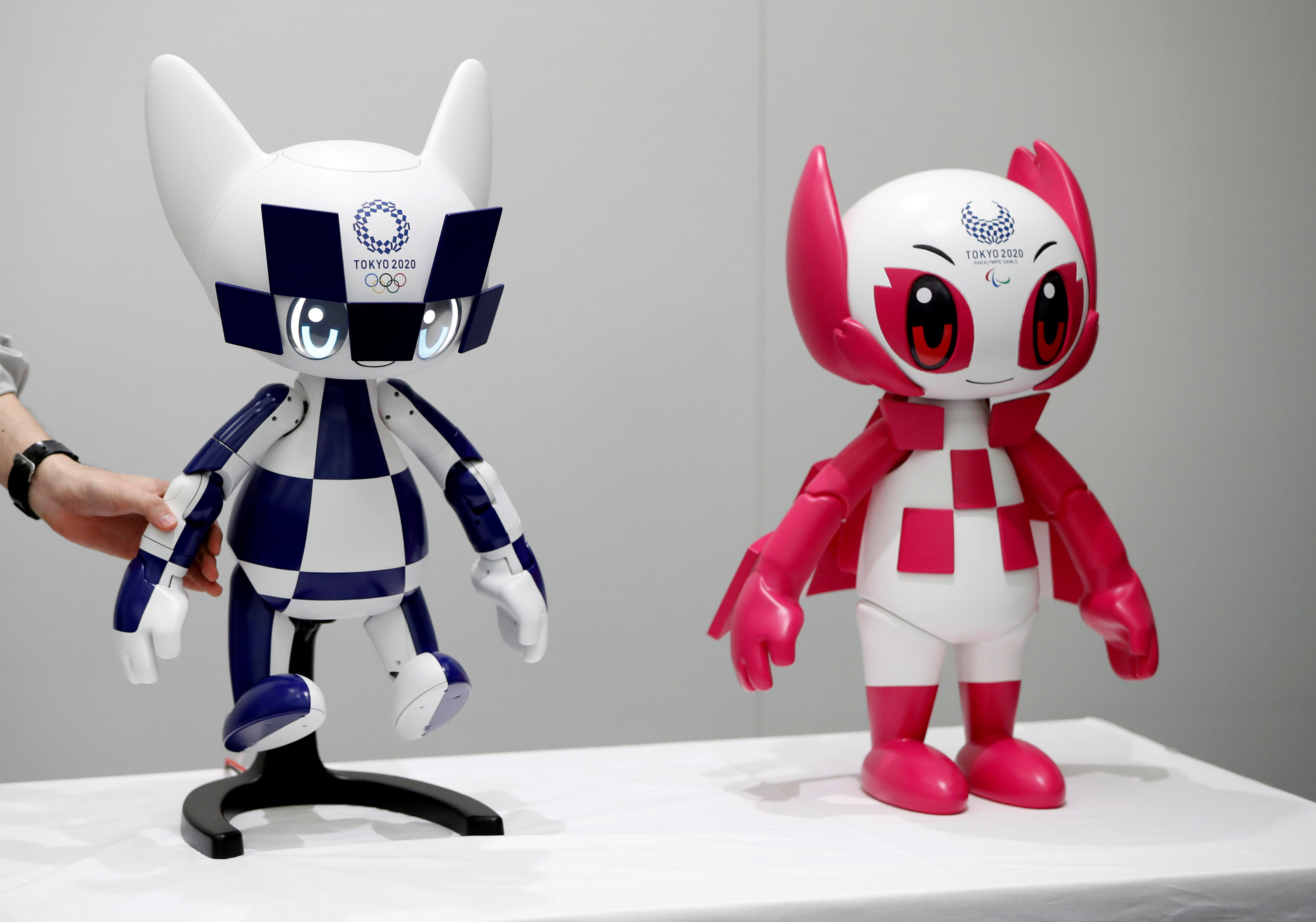 An employee of Toyota Motor Corp. displays Tokyo 2020 mascot robots Miraitowa and Someity which will be used to support the Tokyo 2020 Olympic and Paralympic Games, during a press preview in Tokyo, Japan July 18, 2019. Picture taken July 18, 2019.  REUTERS/Issei Kato - RC1738A83700
