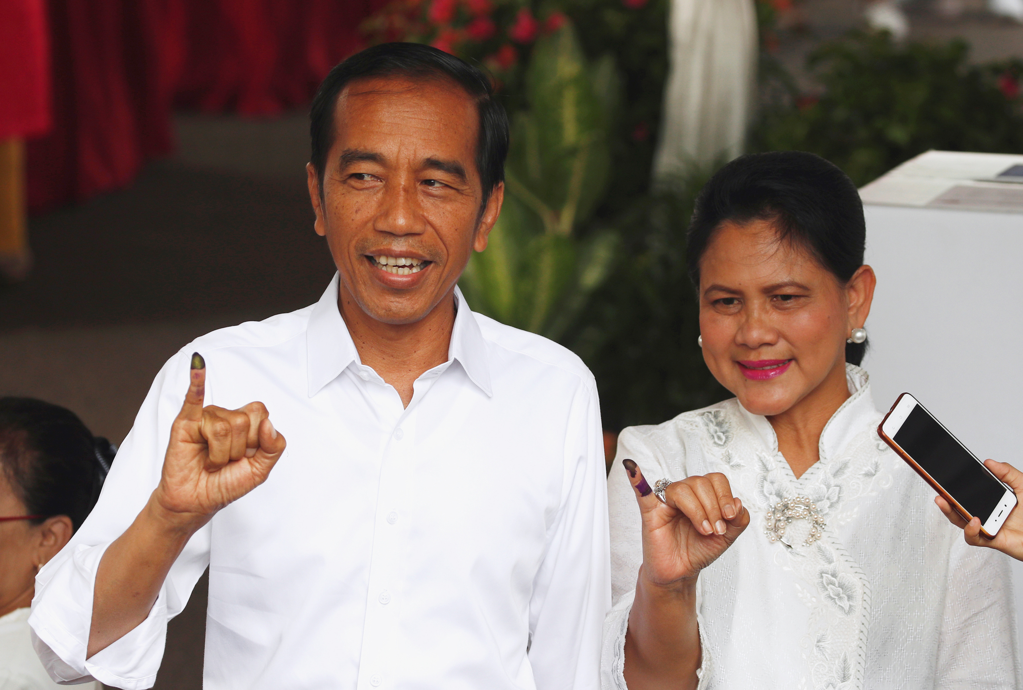 Indonesian President Joko Widodo and first lady Iriana Joko Widodo show their ink-stained fingers after casting their ballots during elections in Jakarta, Indonesia April 17, 2019. REUTERS/Edgar Su - RC1E14849600