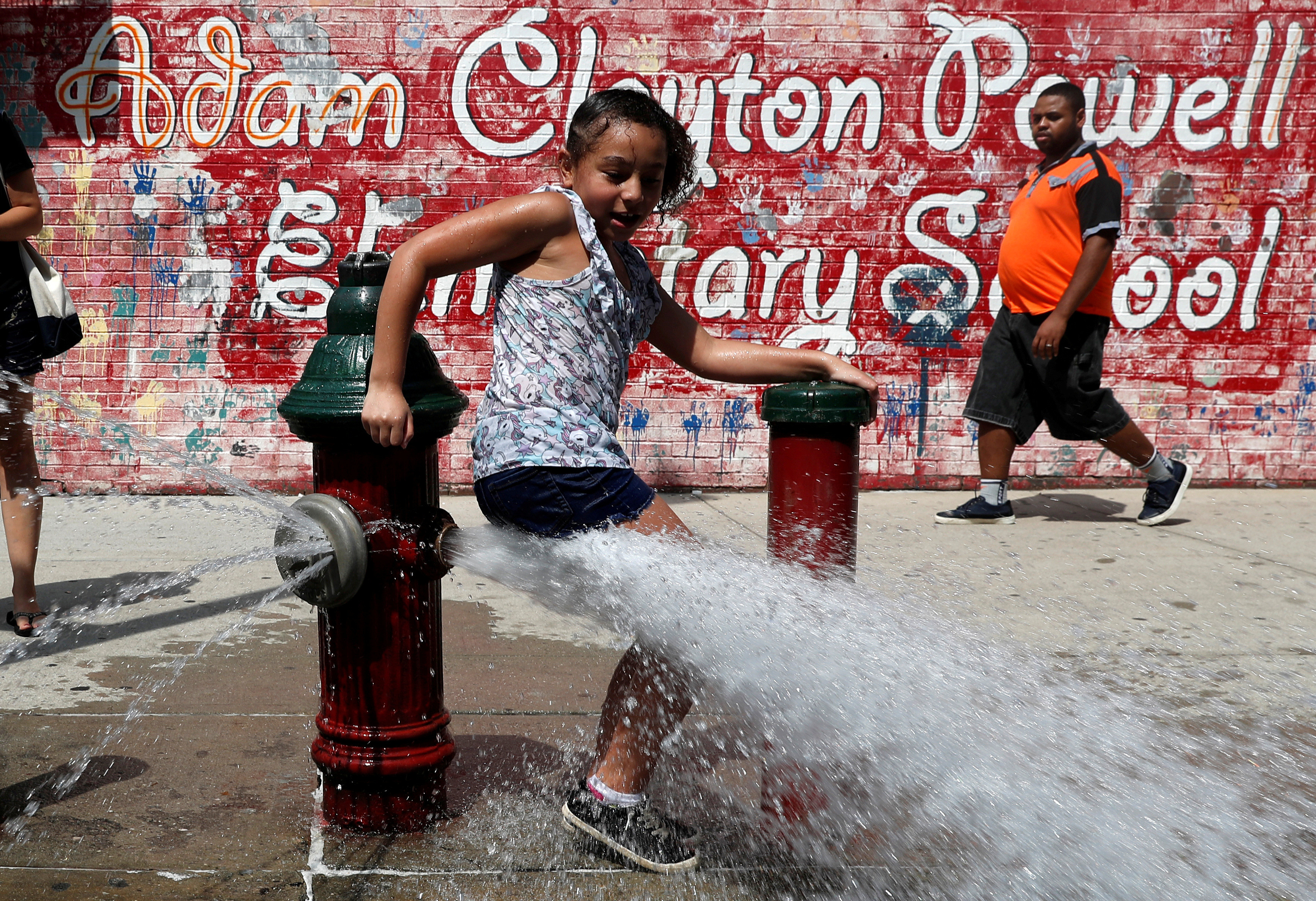 A girl cools off from the heat in water from an open fire hydrant in the Washington Heights section of upper Manhattan in New York City, New York, U.S., July 19, 2019. REUTERS/Mike Segar     TPX IMAGES OF THE DAY - RC12AF9CC5D0