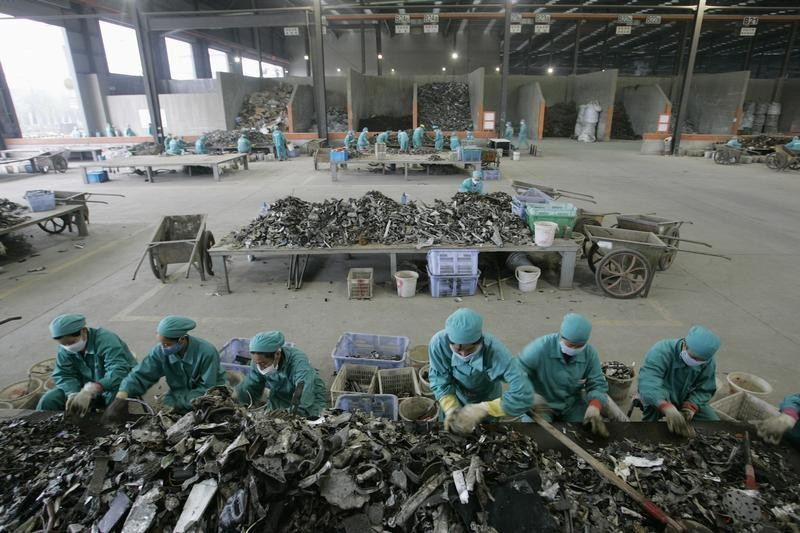 Employees work at a Shanghai Sigma Metals factory in Shanghai November 22, 2006. Shanghai Sigma Metals Inc. plans to increase its aluminium recycling capacity by about 66 percent in the next four years as Beijing's moves to encourage the re-use of metals and on strong demand from car makers. Shanghai Sigma could process up to 500,000 tonnes of aluminium alloy a year by 2010 from 300,000 tonnes this year, company chairman Tony Huang told Reuters November 23, 2006.  Picture taken November 22, 2006.   REUTERS/Aly Song (CHINA) - GM1DTZYCKTAA