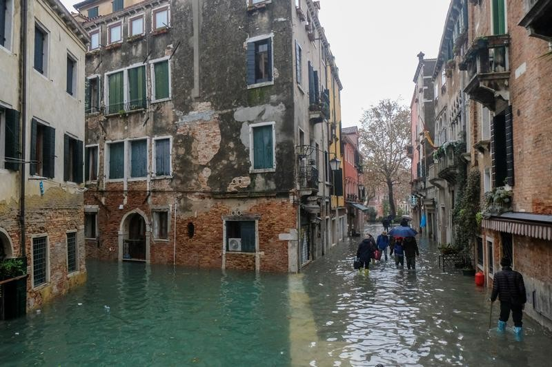 People walk outside during exceptionally high water levels in Venice, Italy November 13, 2019. REUTERS/Manuel Silvestri - RC29AD9M534T