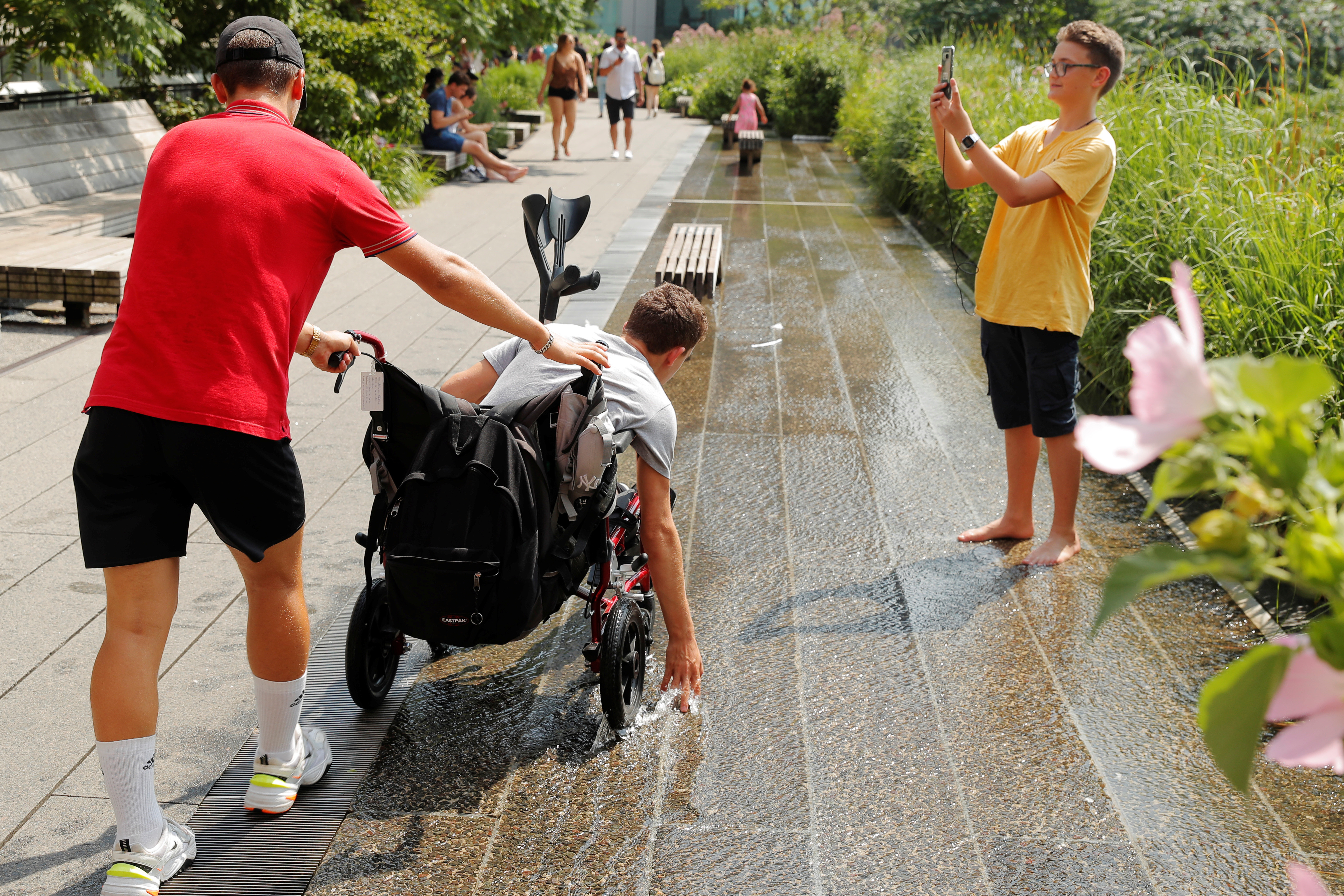 A man in a wheelchair reaches down to touch a water feature in High Line Park during a period of high temperatures in the Manhattan borough of New York City, New York, U.S., July 19, 2019. REUTERS/Lucas Jackson - RC1F35C86D60