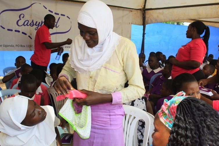 School girls examine a reusable menstrual pad as part of a community event.