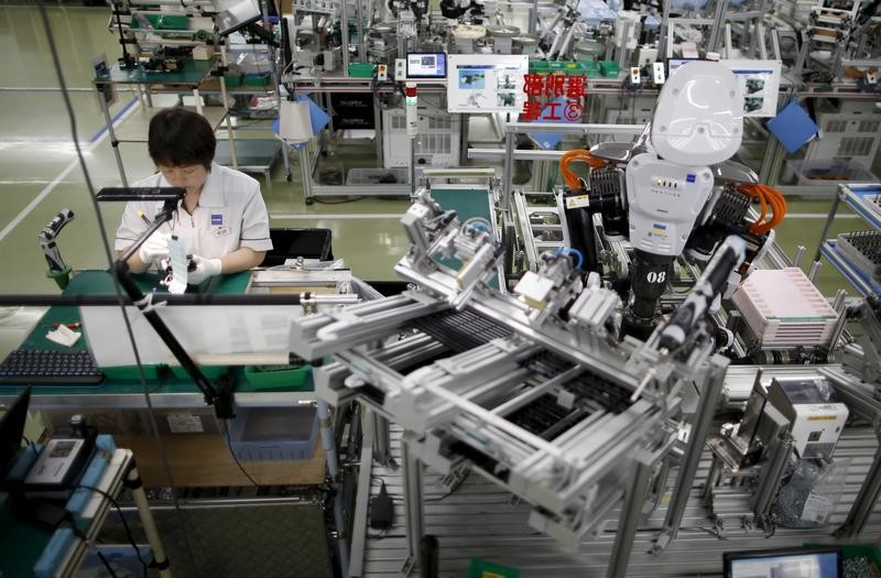 A humanoid robot works side by side with an employee in the assembly line at a factory of Glory Ltd., a manufacturer of automatic change dispensers, in Kazo, north of Tokyo, Japan, July 1, 2015.