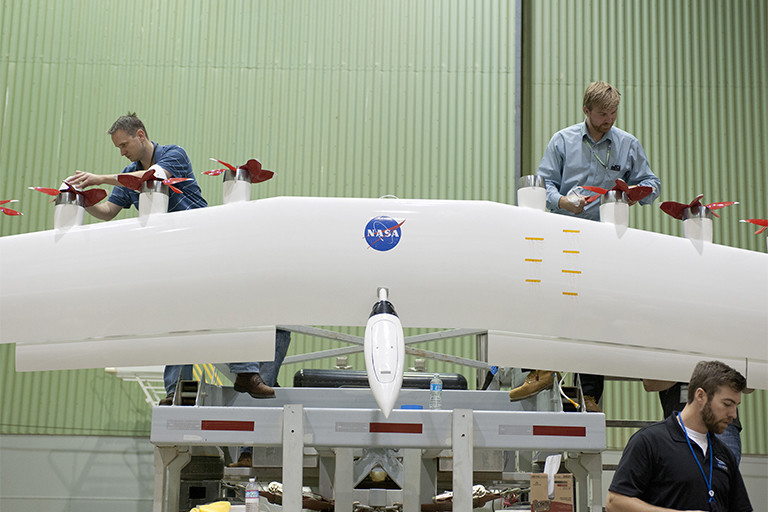 NASA engineers work on the wing of a test electric airplane