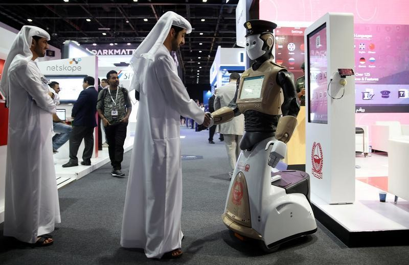 A visitor shakes hands with an operational robot policeman at the opening of the 4th Gulf Information Security Expo and Conference (GISEC) in Dubai, United Arab Emirates, May 22, 2017.