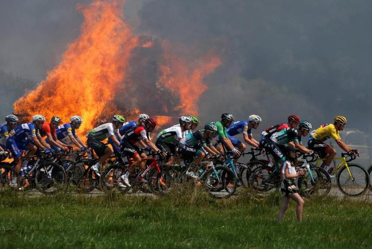 Cycling - Tour de France - The 181-km Stage 6 from Brest to Mur-de-Bretagne Guerleden - July 12, 2018 - The peloton passes a fire. REUTERS/Stephane Mahe