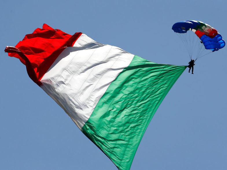 An Italian Army parachutist hoists the Italian flag during the Republic Day military parade in Rome, Italy, June 2, 2018. REUTERS/Tony Gentile