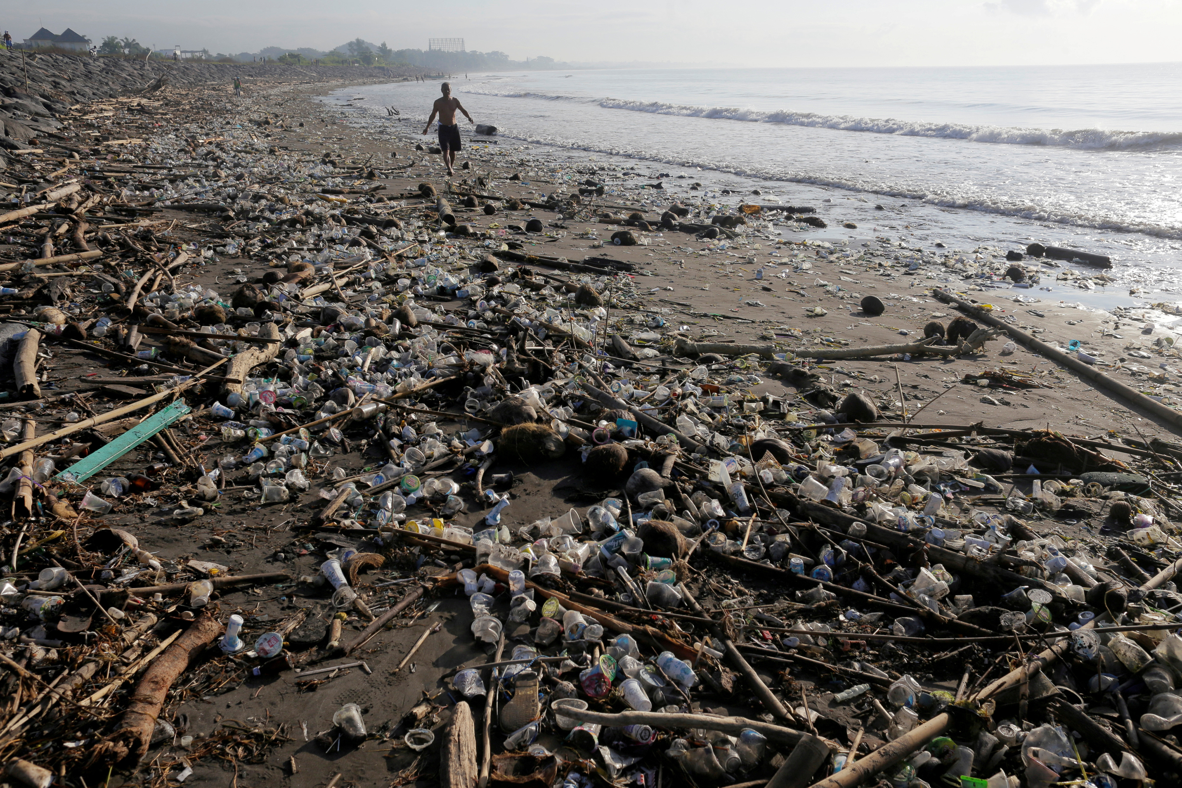 A local resident walks along a section of Matahari Terbit beach covered in plastic and other debris washed ashore by seasonal winds near Sanur, Bali, Indonesia April 11, 2018. REUTERS/Johannes P. Christo     TPX IMAGES OF THE DAY - RC1AF6081DA0