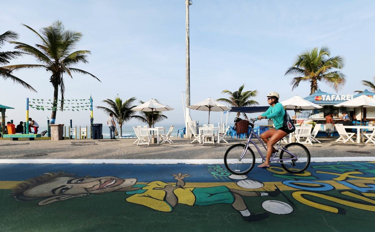 A woman rides her bicycle on Barra da Tijuca beach, July 2, 2018.