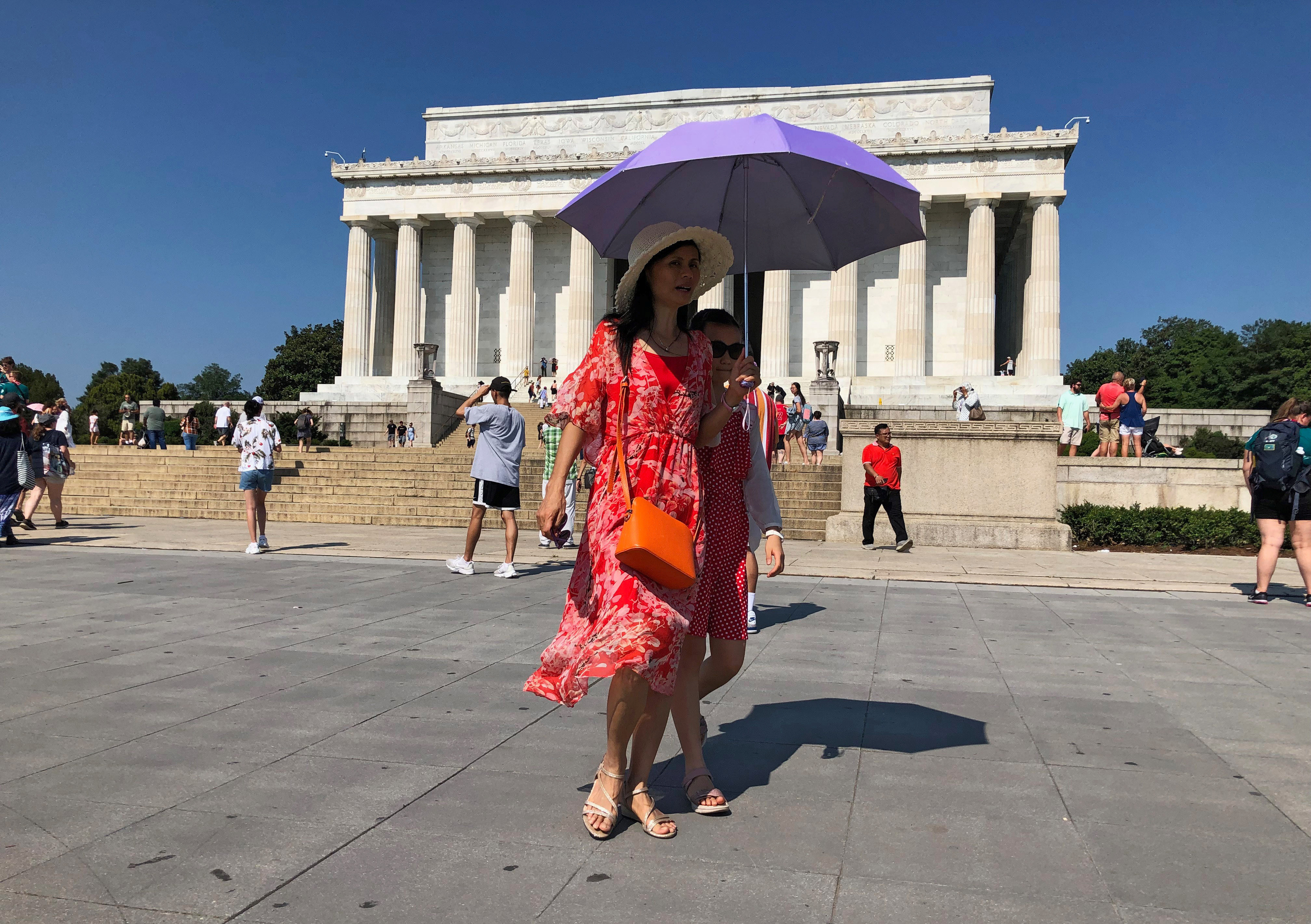A tourist tries to shield herself from the sun using an umbrella in front of the Lincoln Memorial on a day when the temperature was forecast to reach 99 degrees F (37 C), in Washington, U.S., July 21, 2019. REUTERS/Will Dunham - RC19066D0BC0