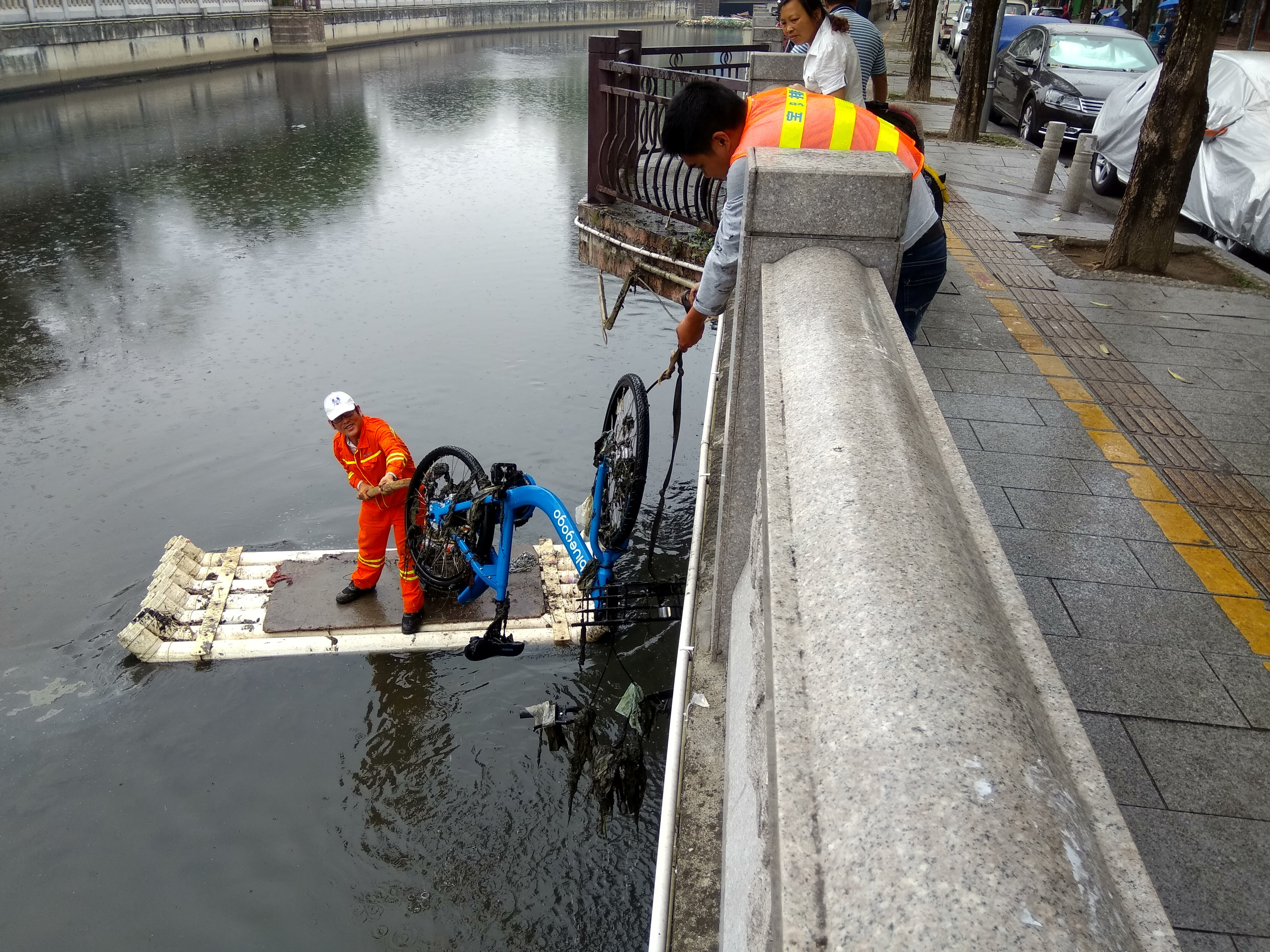 Workers salvage a fallen sharing bicycle from a river in Shenzhen, Guangdong province, China, April 24, 2017. Picture taken April 24, 2017. REUTERS/Stringer ATTENTION EDITORS - THIS IMAGE WAS PROVIDED BY A THIRD PARTY. EDITORIAL USE ONLY. CHINA OUT. NO COMMERCIAL OR EDITORIAL SALES IN CHINA. - RTS13SD0