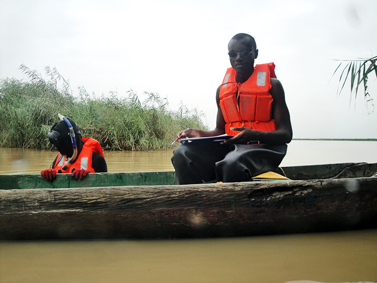The field team uses a wooden canoe and protective clothing during snail sampling at Kheune, Senegal.