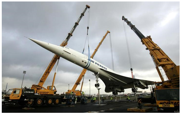 The retired Air France Concorde number 5 is lowered by cranes onto pylons on the tarmac at the Roissy-Charles de Gaulle Airport, north of Paris October 19, 2005. The retired Concorde is placed on permanent display in an inclined position to simulate the take off of the supersonic passenger jet.