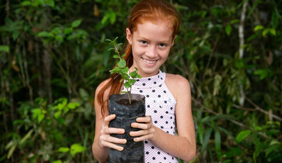 Marlice Soares, 9, holds a native tree seedling planted in her family's agroforestry system in the Brazilian Amazon