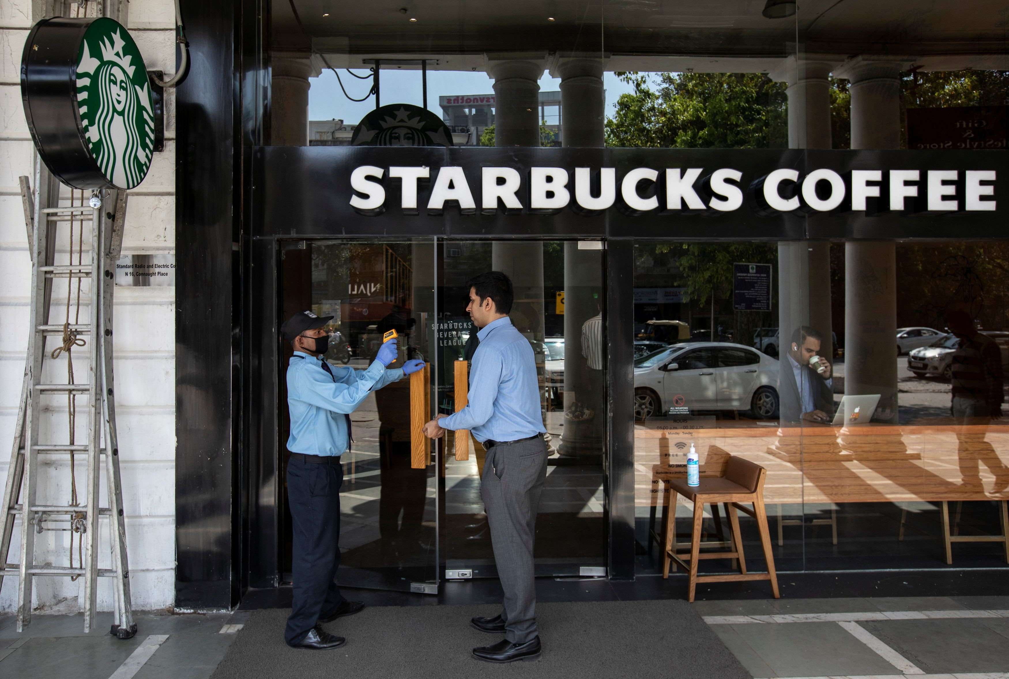 A private security guard checks the body temperature of a customer outside a Starbucks coffee shop, as a precaution against the spread of coronavirus, in New Delhi, India, March 17, 2020. REUTERS/Danish Siddiqui - RC2JLF9GMI5O